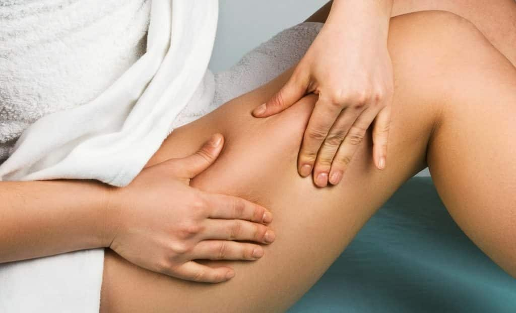 cellulite massage, performed by a woman on herself