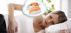 blond woman in white t-shirt, doubled over in pain, lying in bed, with thought bubble displaying salmon fillet