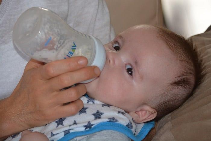 baby taking in a bottle