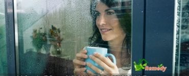 woman looking at window on rainy day