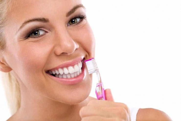 young blonde woman with very white teeth and pink toothbrush