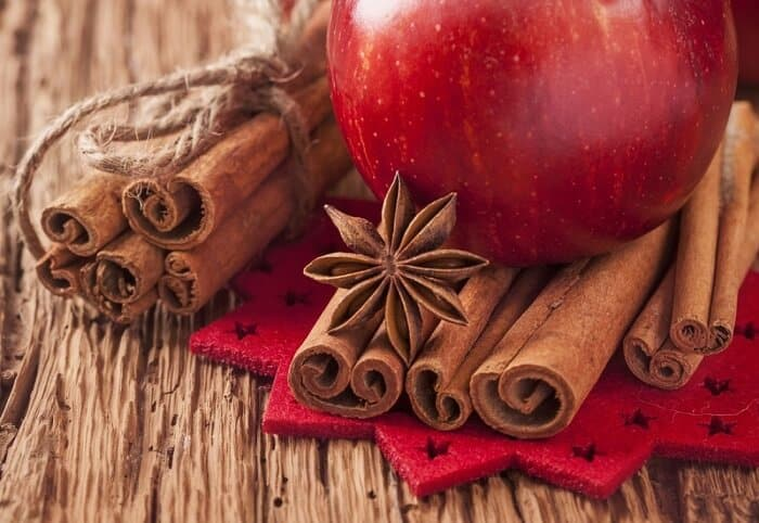 cinnamon with red apple on table