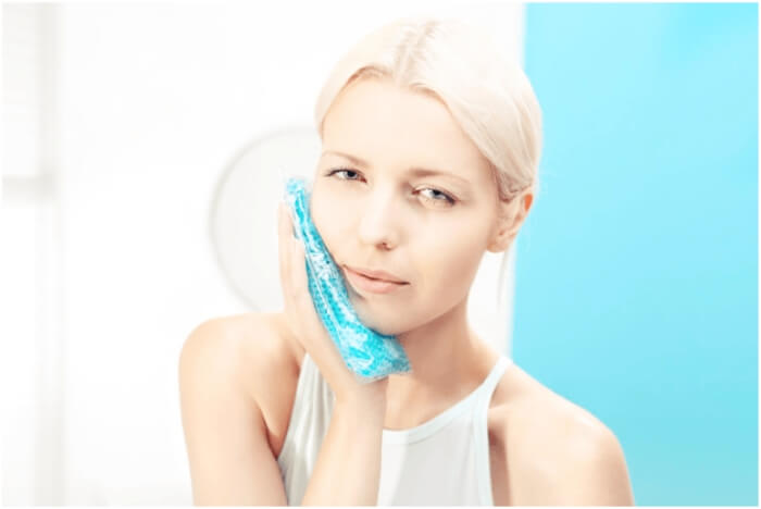 woman pressing cold compress on cheek neck