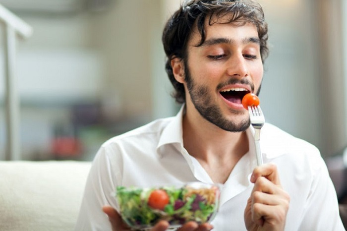 man in white shirt eating a salad