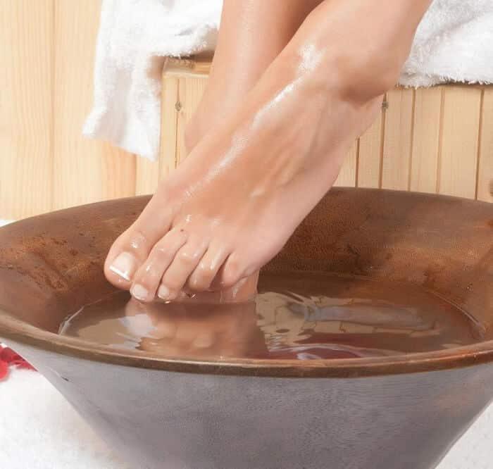 closeup on someone soaking feet in water