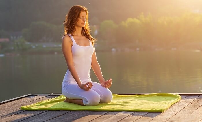 woman doing yoga near a lake