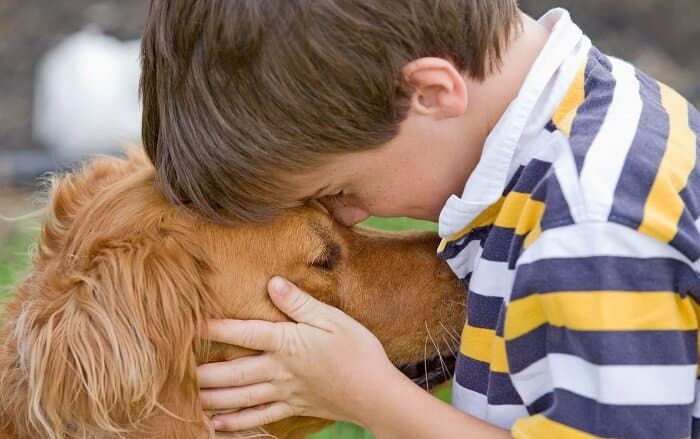 little boy holding his dog
