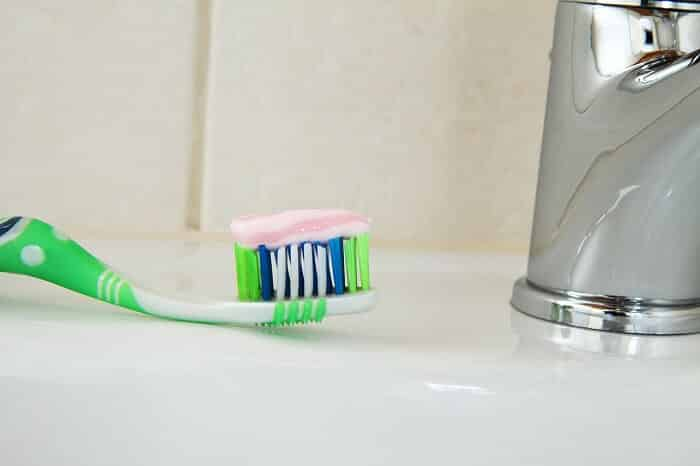 toothpaste on a toothbrush in the bathroom