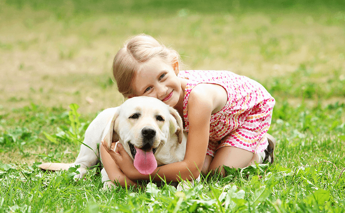 little girl holding her dog tightly
