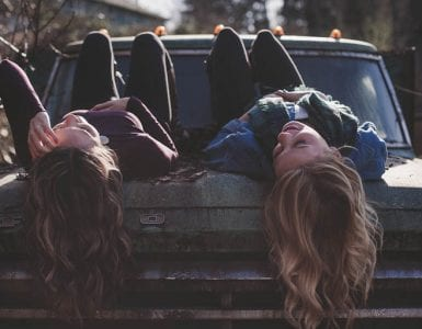 two woman lying down on a car