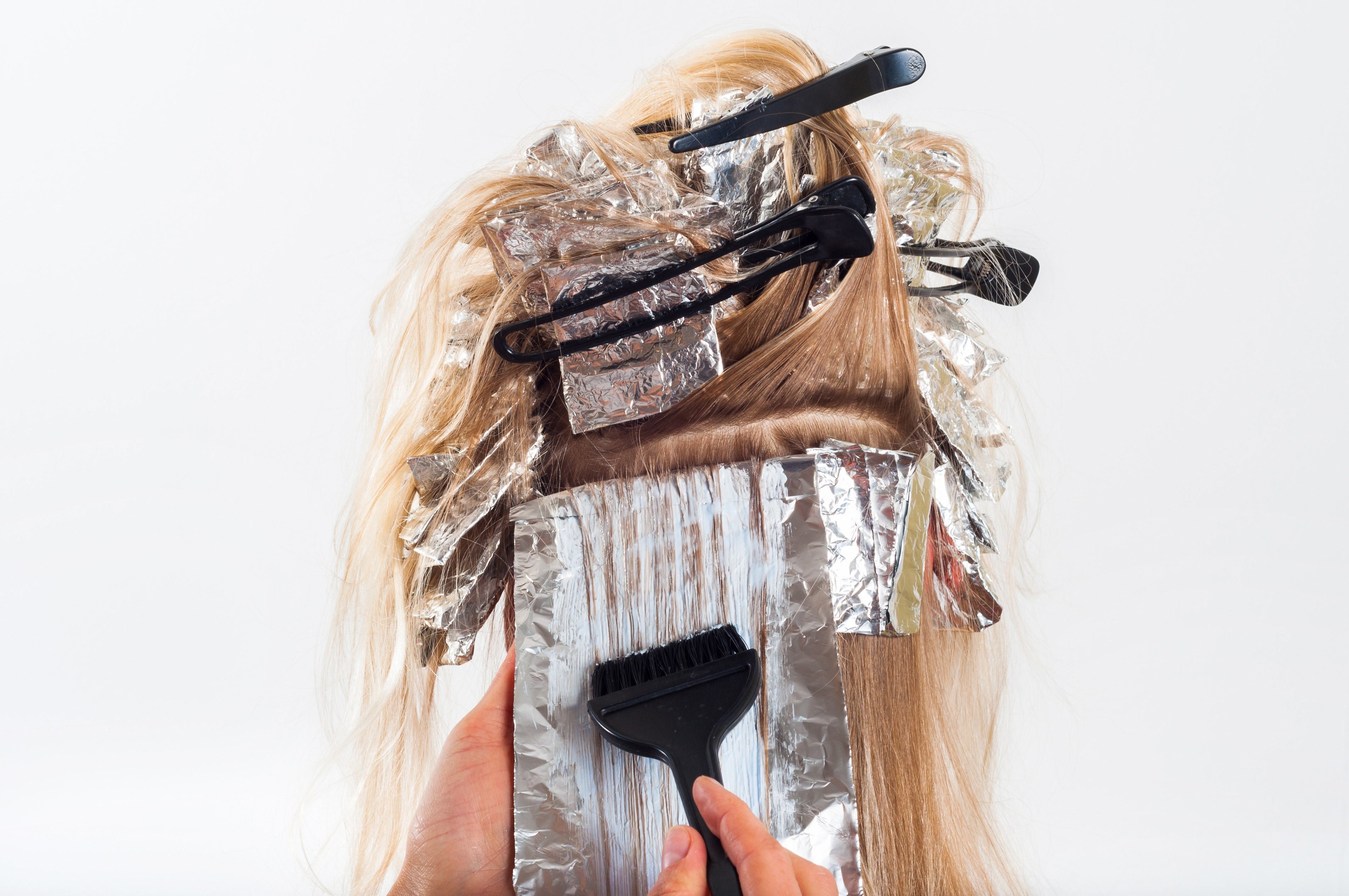 a blonde woman having her hair treated with natural hair product with brush and foil