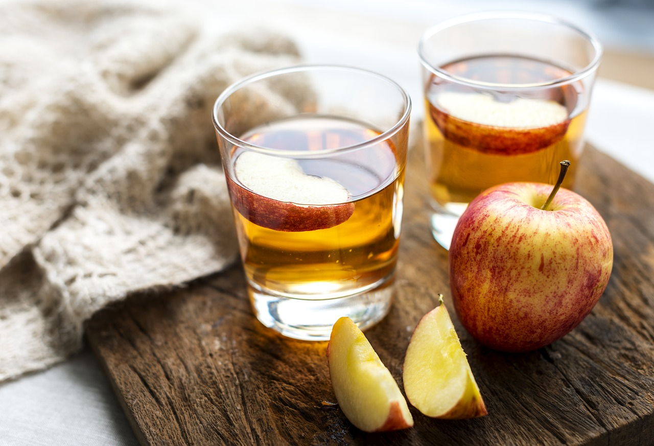 two glasses of apple juice and fresh slices and whole apples