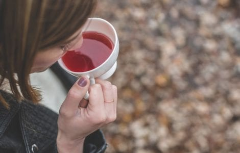 a woman drinking tea, a home remedy for ovulation pain