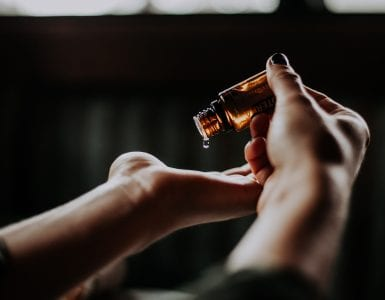 close-up photo focused on essential oil on amber bottle about to be poured into left hand