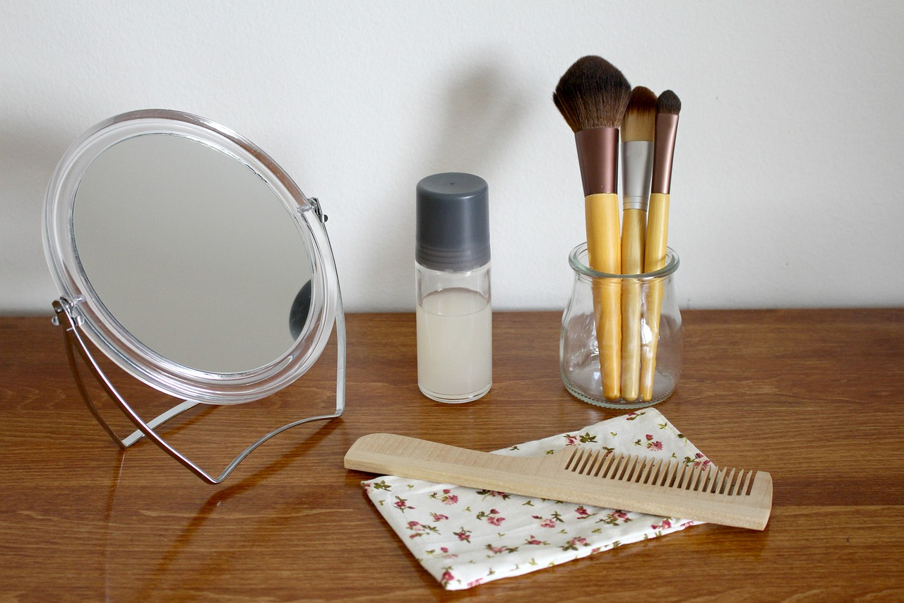 a natural hair product in a small small container, a compact mirror, comb and make-up brushes