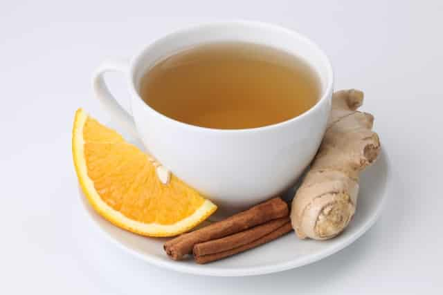 Cup of orange tea with cinnamon and ginger on white background. Shallow dof