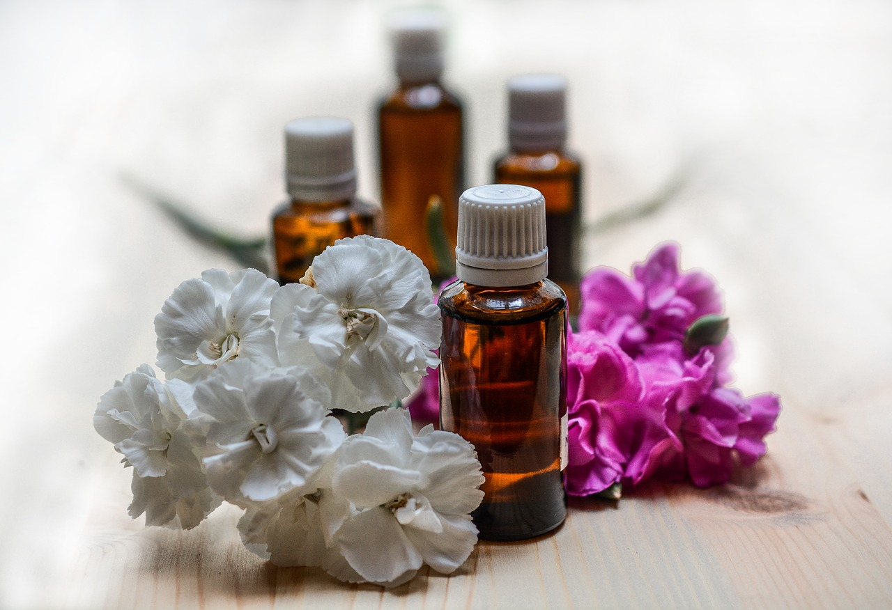 different essential oils for bronchitis on amber bottles and fresh flowers