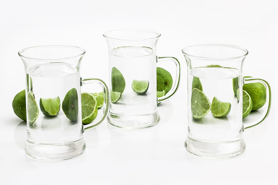 three glasses of water and sliced calamansi citrus fruit