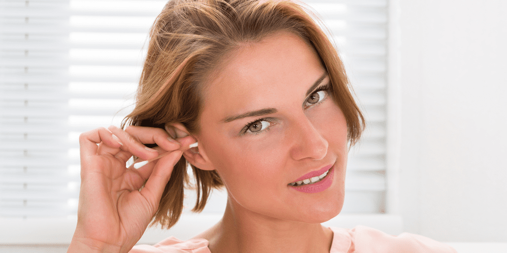 a woman showing how to clean your ears with cotton swab