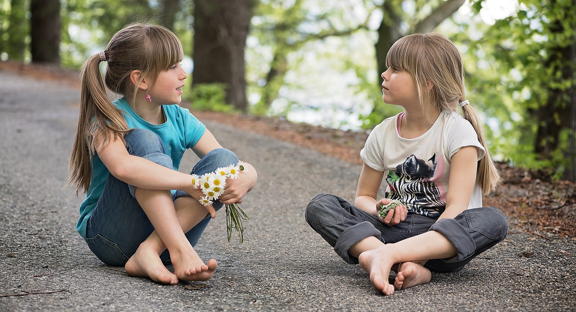 2 girls is seating at the road in the park and having a conversation