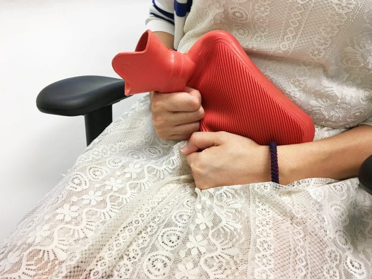 a woman using hot compress, a way to induce period