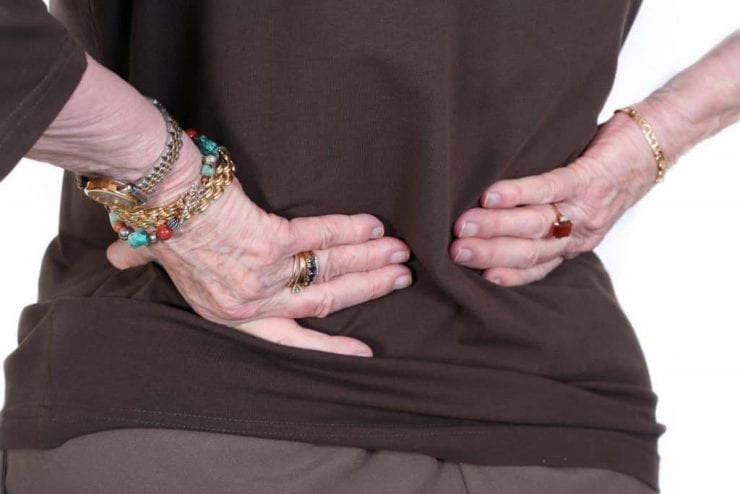 Elderly woman experiencing lower back pain