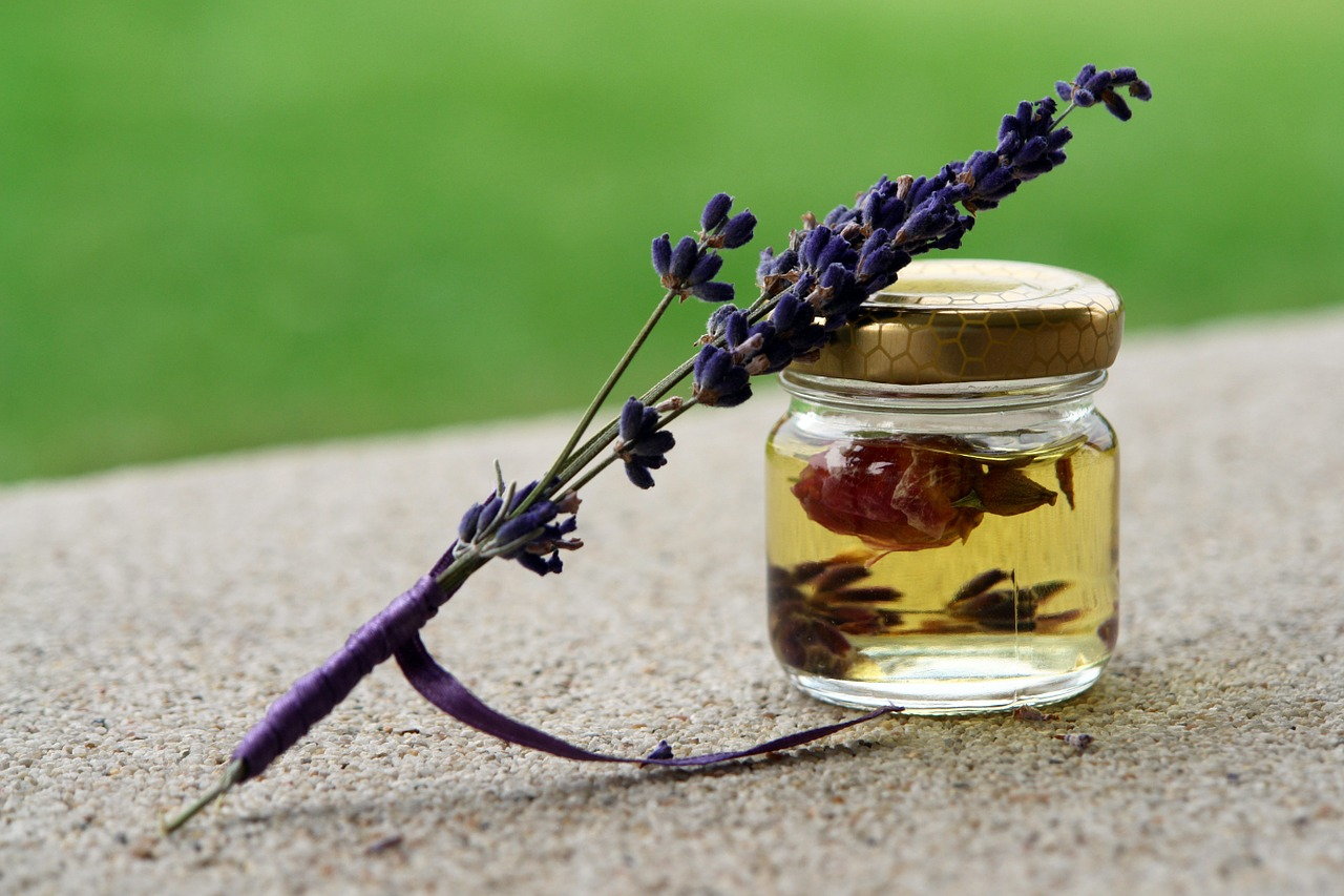 a small bottle of rose essential oil and a fresh lavender flower, commonly used to add fragrance unto natural detergent