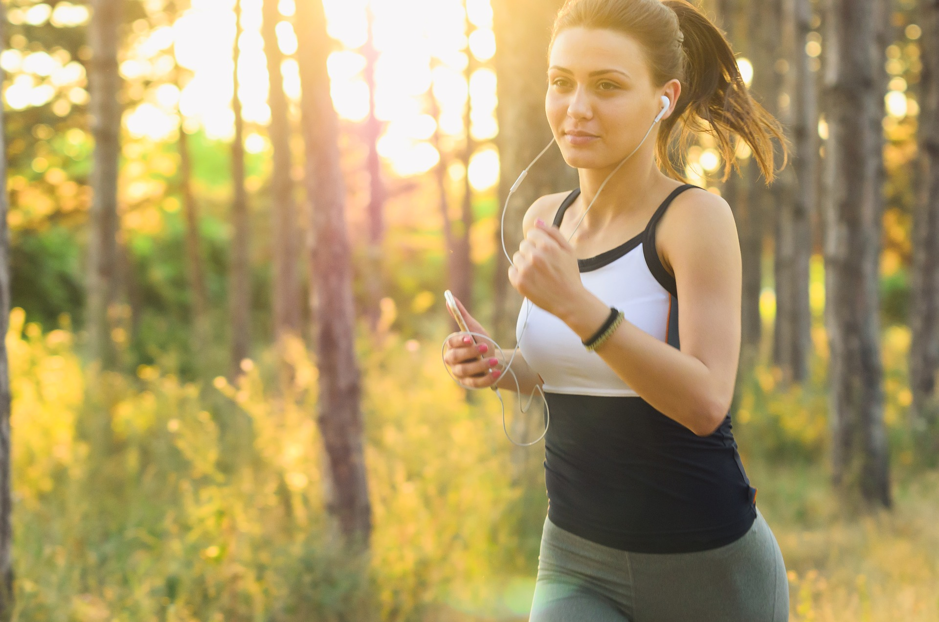 girl holding a phone and wearing a headset is doing some jogging at the park