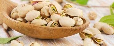 health benefits of pistachios in a wooden bowl
