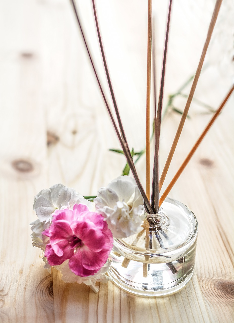 photo of scent sticks with essential oil on glass container