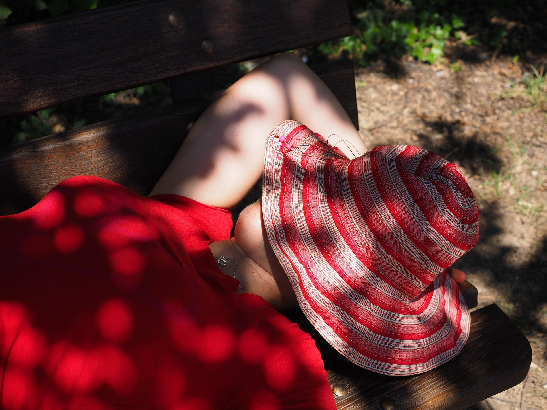 Girl covering her face with a red hat is taking a nap at the bench outside the house