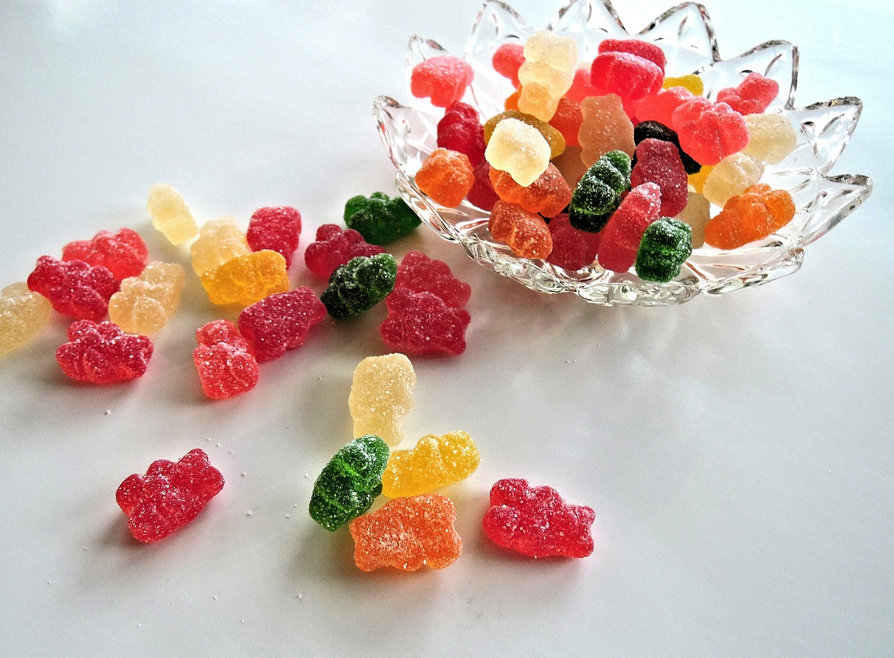 sour candy on a small glass bowl and more candies scattered on the surface