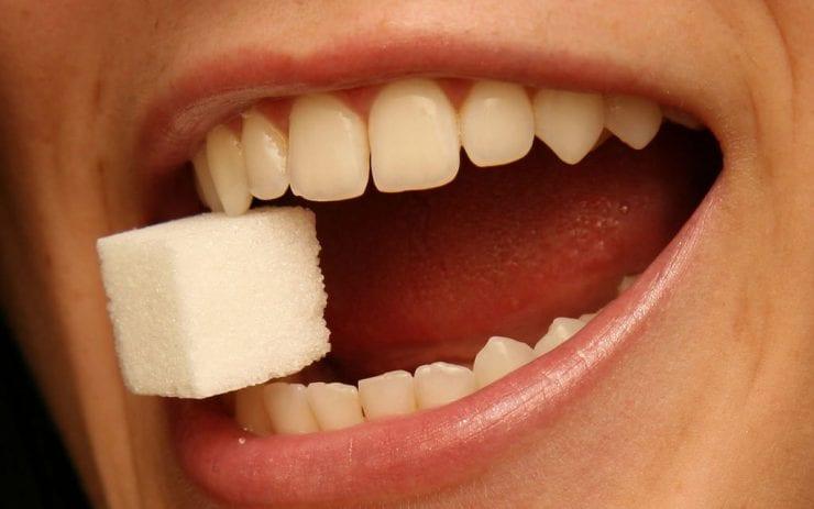 teeth biting a sugar cube